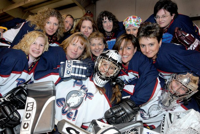 Members of the Puck Ewes stop to pose for a photo before their season-opening game Saturday. The Ewes, a women's team of about 15 players, spend a few hours a week on the ice, making their dreams of playing hockey come true.