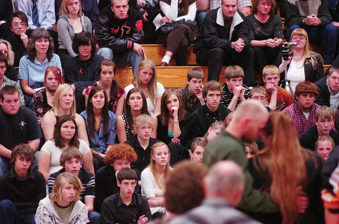 "Hayden High School students watch as Charlie Donelson consoles his wife, Shannon, during a memorial service for their son, Robert ""Bobby"" Donelson. Friday's service was held in the school's gymnasium three days after Bobby collapsed and died on the school's football field."
