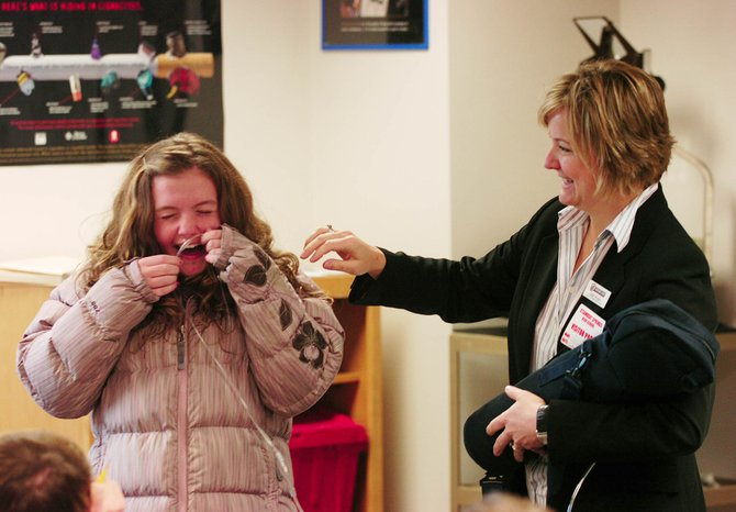 Steamboat Springs High School sophomore Jessie Dunlop laughs while PS Homecare sales representative Cari Pugh helps her put on an oxygen tube so she can learn what it is like to be on supplemental oxygen. Students in Luke DeWolfe's health class were learning about respiratory ailments associated with smoking as part of the American Cancer Society's Great American Smokeout.