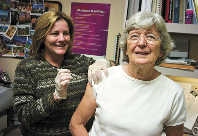 Ellen Carlson, right, gets her annual flu shot from nurse Wendy Bower at the offices of the Northwest Colorado Visiting Nurse Association in Steamboat Springs.