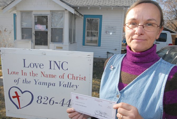 Love INC Executive Director Patricia Jones holds up a $5,000 check from the El Pomar Foundation, which she received Monday. Jones said her organization will decide how to use the money at a board meeting Dec. 18.