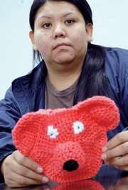 Billie Colorow holds a crocheted bear she made for her daughter.