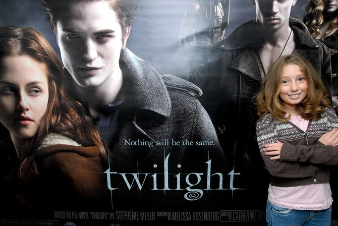"Haleigh Rodela, 9, poses for a photo in front of a poster for the movie ""Twilight,"" which opened Nov. 21 at West Theatre in Craig. Rodela, of Arvada, is the granddaughter of Debbie Winder, West Theatre manager, but she is among a large number of youths across the country who are fans of the book and movie."