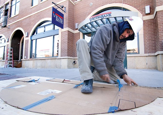 Joseph Naranjo, of Western Valley Glass, works to put the finishing touches on Howelsen Place. When finished, Vectra Bank plans to move into the new building down the street from its current location.