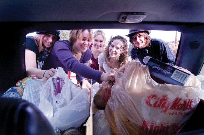 Soroco High School student council members, from left, Felica Starks, Ashton Martinez, Bethany Leu, Chelsea Nason and Cameron Lichnovsky unload food to be donated to the LIFT-UP of Routt County's food bank at the Oak Creek Community Center.  The school's food drive collected 350 items.