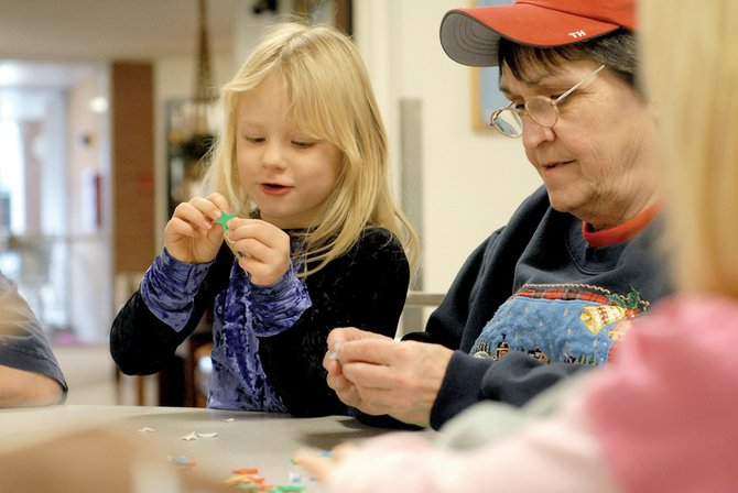 Emily Gagon, left, works on Christmas decorations with Connie Sickle on Wednesday at Sunset Meadows. Girl Scout troops 3557 and 3269 stopped by Sunset Meadows to make decorations with residents and get them in the holiday spirit.