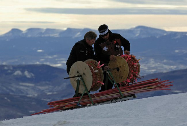 With the Flat Tops in the background, Mike Hodder, left, and Chris Welch load a work sled with materials to be used on the upper mountain in preparation for its opening this weekend. The ski area's avalanche team will be back at it today for more control and set-up work.