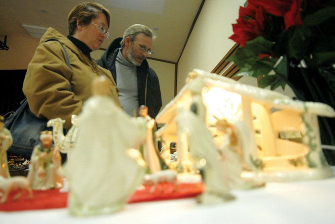 Steven and Monique Arnold look at Nativity Sets Thursday at The Church of Jesus Christ of Latter-Day Saints in Craig. The sets are part of an annual display showcasing Nativity Sets. This year, the exhibit contained 488 entries.
