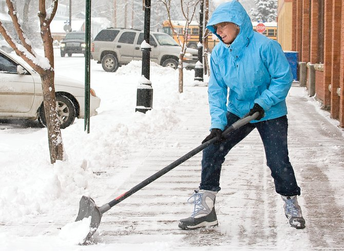 Tahnee Miller shovels snow in front of Lyon's Drug in downtown Steamboat Springs this morning. A winter storm is expected to persist throughout the day, with 4 to 8 inches expected at higher elevations, including the ski area.