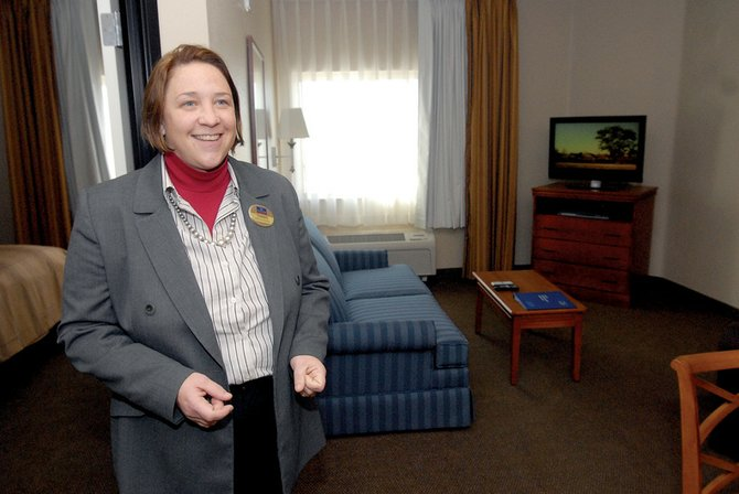 "Tammie Thompson-Booker, director of sales for Candlewood Suites, shows one of the new building's largest rooms, a one-bedroom suite with a separate living room. Thompson-Booker said she ""fully expects"" the hotel to be at ""operating capacity"" - 60 to 70 percent full - by the end of March."