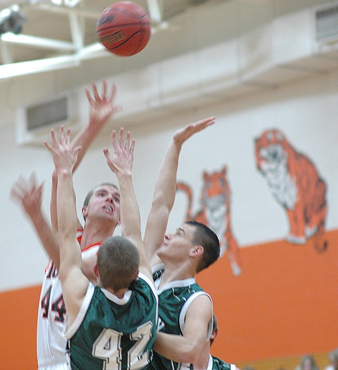 Hayden senior Zach Barnes lofts a shot over a pair of Rangely defenders Friday. Barnes found plenty of room to operate in the lane against the shorter Panthers and led all scorers with 19 points. It wasn't enough to keep the Tigers from their first loss of the season, however. Hayden fell, 55-52.