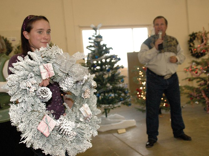 Heather Nereson, 12, displays a wreath, crafted by the Hayden Valley Elementary Gift Festival for Sunday's Christmas Tree Auction in Hayden, as auctioneer Kenny Kawcak calls the auction to the crowd. Mountain Valley Bank purchased the piece, which was one of several dozen up for auction, for $50.