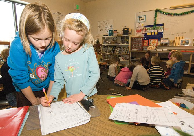 Third-grader Katie Saunders helps first-grader Lydia Noble with her classwork at Strawberry Park Elementary School. The students are part of the Montessori program at the school. The program's success is attracting attention from parents and students, but only six to eight openings are available to a waiting list of 21.