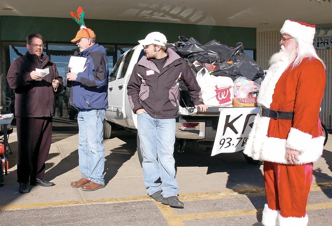 The Kiwanis Club of Craig donates $800 Wednesday to the KRAI 55 Holiday Drive. Kiwanis Club member Bryce Jacobson, left, presented the check to KRAI owner and general manager Frank Hanel and challenged the Rotary and Lions clubs to match the donation. Also pictured are a holiday drive volunteer and Santa Claus. The Holiday Drive continues today at the west entrance to Centennial Mall and wraps up at 6 p.m. Many businesses, individuals, families and civic groups have contributed money, toys, bicycles and more at the drive.