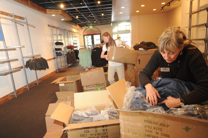 Anne Gillespie, visual merchandiser for Steamboat Ski and Resort Corp., looks through a box of merchandise Wednesday while setting up the new Steamboat Ski & Sport Downtown Howelsen Place store with retail shop employee Heidi O'Steen. The new store will open Saturday.