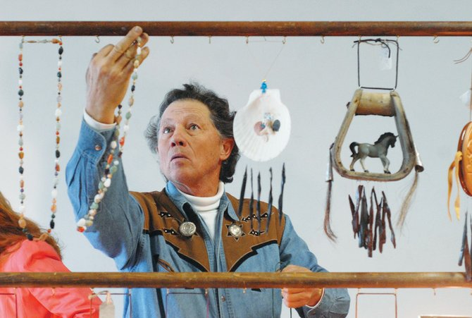 "Glenn Pritchard hangs up ""Begger Beads,"" hand-made by his wife, Audrey, along with wind chimes at the 2007 Winter Arts and Crafts Show at Centennial Mall. The 2008 show continues from 9 a.m. to 4 p.m. today at Centennial Mall."