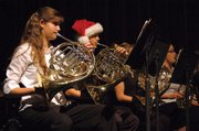 Holiday spirit is in the air Tuesday night, as French horn player Chris Griffin dons a Santa hat during the Moffat County High School Concert Band's winter concert. Several other band members also wore holiday-themed hats and headbands, some featuring reindeer antlers.