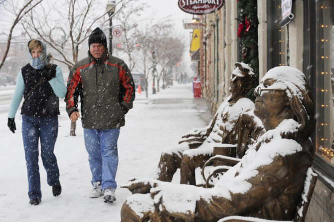 Florida residents Linda and Alex Stearns walk past snow-covered Ben Franklin and Abraham Lincoln bronze statues Friday in front of Wild Horse Gallery Downtown at Eighth Street and Lincoln Avenue.