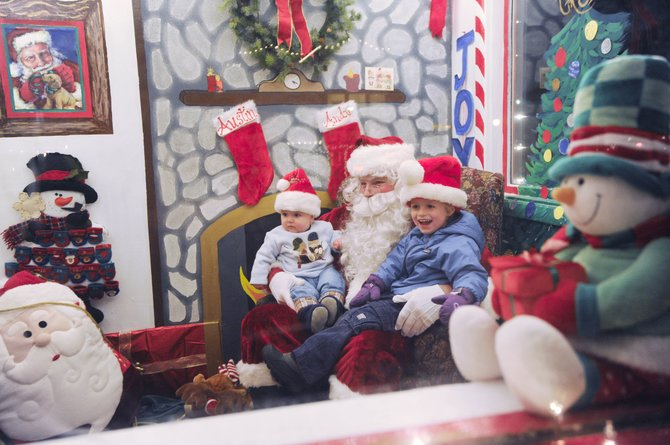 Three-year-old Eli Ince and his 8-month-old brother, Henry, visit Santa on Saturday during the Merry Mainstreet Downtown Holiday Celebration on Lincoln Avenue.