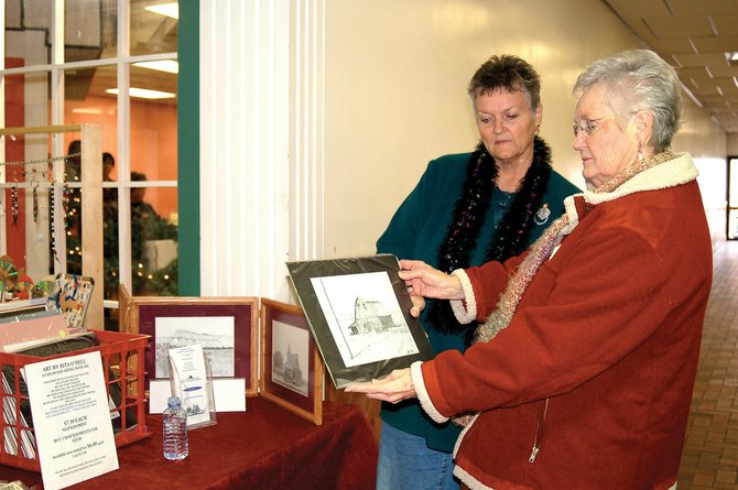 Deanna Messing, right, of Craig, looks at a drawing Saturday at the Winter Arts & Crafts Show at Centennial Mall, as her sister, Leslie Kirk, looks on. Messing, who is an artist, marveled at some of the artwork for sale at that booth, which was done using a stipple technique, she said.