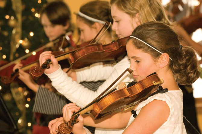 Lowell Whiteman Primary School students, from front to back, Dominique Katthain, Madeline Craig-Scheckman, Eliza Leason and Drew Williamson play a holiday tune at the community center's senior luncheon Monday afternoon.