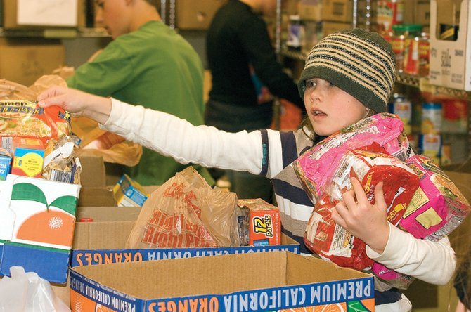 North Routt Community Charter School fifth-grader Grace Mark sorts through food at the LIFT-UP of Routt County Food Bank on Monday morning. The elementary school students volunteered their time to help the food bank stock recently donated food items.
