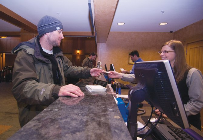 Visitor Andrew Fenet is helped by Kristen Willie while checking in at the Steamboat Grand earlier this week. Bookings for the holidays are down by about 15 percent, which is a smaller difference than what has been projected for the holidays.