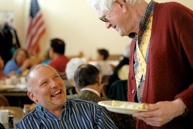 Congregation member Tim Guinn, left, shares a laugh with Tom Ward at the Faith Lutheran Church free Christmas dinner Thursday. The congregation hosted the dinner, which was open to the public.