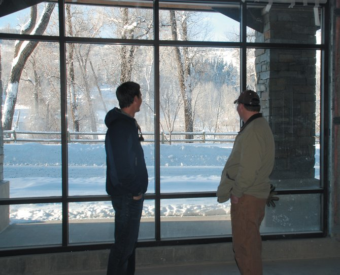 Owner Tim Kirkpatrick, right, and Realtor Brian Ladd admire the view of cottonwoods along the Yampa River from the future home of Steamboat Flyfisher in The Olympian.