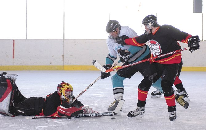 The Oak Creek Kodiaks' Kyle Dimmitt crashes into the Crested Butte goalie during the February 2007 Winter Fest hockey match.