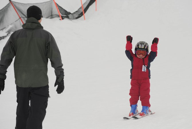 Mac Redfern, 3, of Steamboat Springs, throws his arms up in victory at his father Neill after completing a short run on Christmas Day at Howelsen Hill. Skiers and riders likely will be enjoying powder conditions today as a winter storm hits western Colorado. Visitors to Steamboat Ski Area will have access to several lifts that open 15 minutes early today through Wednesday.