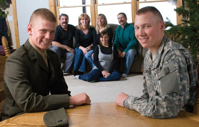 The families of Marine Pvt. Joe Nerney, left, and Army Pvt. Alex Palaniuk, right, got an early present when their sons returned home for the holidays. Joe's parents, Kevin and Kathy Nerney (seated behind Joe), and Alex's family, from left, Diane Anderson, Angela Palaniuk and Joel Anderson (seated behind Alex), were thrilled to have the boys home.