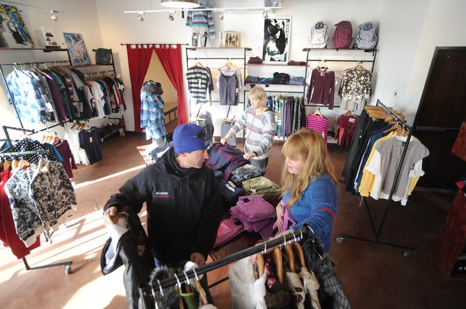 Urbane clothing store owner Trent Kolste, back, folds a shirt while fellow owner Mel LeBlanc, right, helps customer Bob Garber shop for his daughter Wednesday at the store located in Howelsen Place at the corner of Seventh Street and Lincoln Avenue.