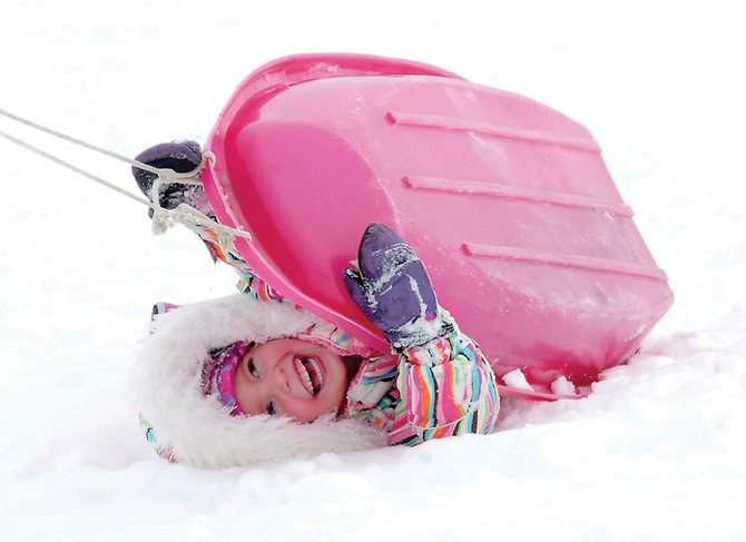 Cassie Haley, 4, laughs after her sled tips over in front of Moffat County High School on Sunday. Haley headed out with her family to enjoy the winter weather.