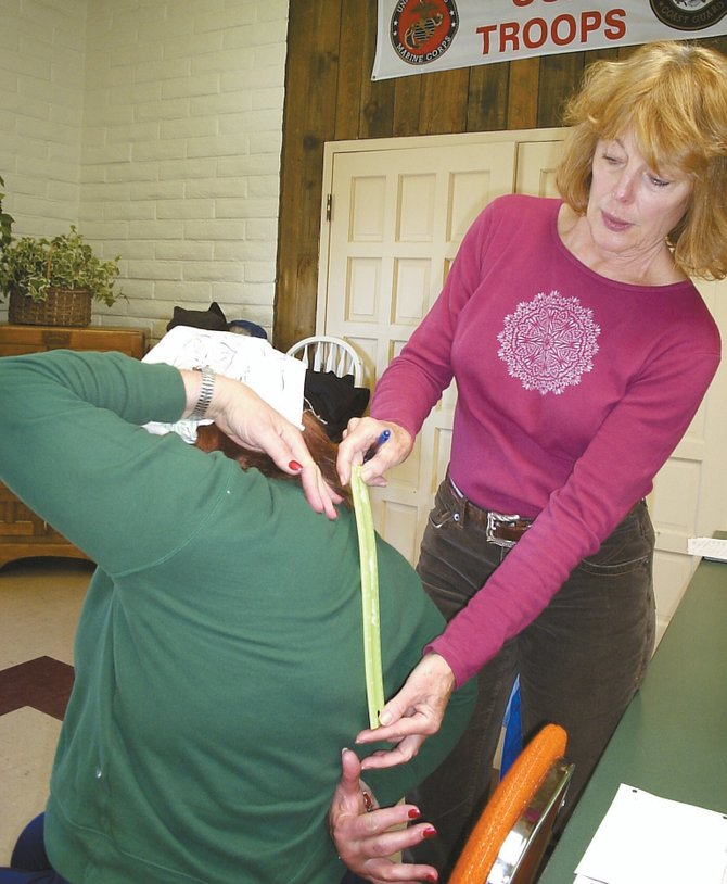 Aging Well fitness coordinator Jeanne Upbin tests a participant's flexibility during a fitness test at Wellness Wednesdays in Craig. The VNA's Aging Well program will offer similar fitness activities and other opportunities for adults 50 and older during Hayden Wellness Days, held Wednesdays beginning Jan. 7 at the new Haven Community Center.