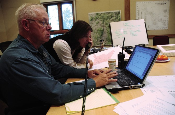 Routt County Emergency Management Director Chuck Vale works in September 2007 at an incident command center in Centennial Hall, dealing with water problems in Steamboat Springs. Also pictured is city management employee Wendy DuBord. After 17 years of county service, Vale has accepted a state position that begins Jan. 12.