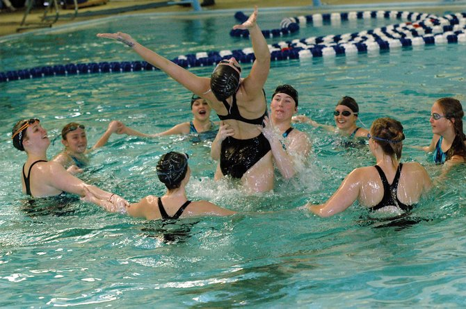 The Moffat County High School varsity girls swim team celebrates Saturday at the conclusion of their lone home meet of the season. The Bulldogs won at home for the fifth consecutive year.
