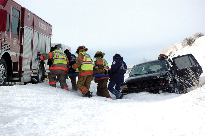 Craig Fire/Rescue firefighters and The Memorial Hospital emergency medical personnel carry a 41-year-old man Monday morning to a waiting ambulance on the side of U.S. Highway 40 less than a mile east of Craig. A Colorado State Patrol official reported that the man seemed to have lost control of his 1999 Dodge Durango while taking a left-hand curve, which caused him to slide across the road, roll over once and come to a stop in a roadside ditch. The driver reportedly went to TMH for medical attention, but he did not suffer life-threatening injuries. Two dogs were also in the car but were unharmed.