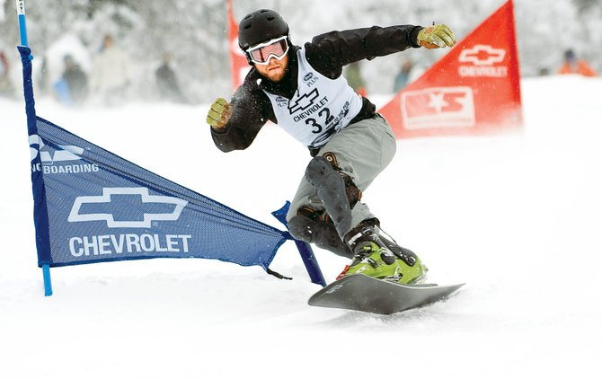 Steamboat Springs snowboard racer Darren Ratcliffe takes an aggressive line in the qualifying round of the Race to the Cup NorAm event Friday night at Howelsen Hill. Ratcliffe defeated teammate Mike Trapp to win the slalom race. The racers will return for the parallel giant slalom today at Howelsen. Races are scheduled to start at 11:30 a.m.