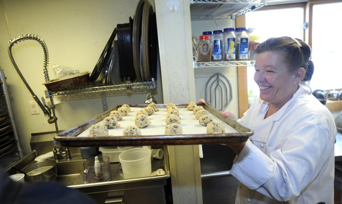 Sharon Stone, who runs the City Cafe in Centennial Hall, carries a tray of cookie dough to the oven Tuesday morning.