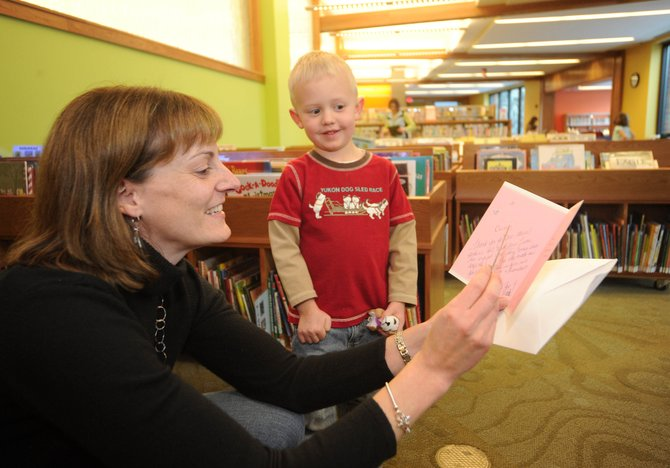 Bud Werner Memorial Library children's librarian Currie Meyer reads a card given to her by 4-year-old Lucas Smith, of Steamboat Springs, on Friday afternoon in the children's department at the library. The library invited people to come say goodbye to Meyer, who is moving to Fort Collins after eight years at the Steamboat library.