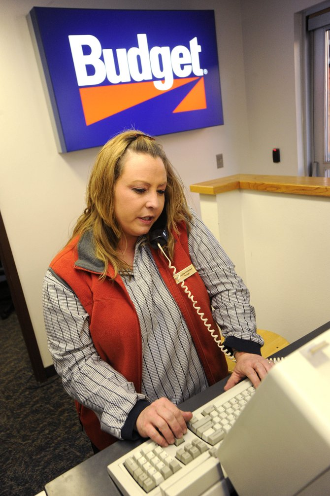 Budget Rent A Car manager Audra Holmes talks to a customer on the phone Thursday at Yampa Valley Regional Airport.