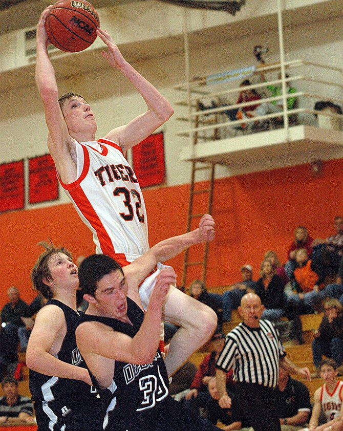 Hayden's Murphy Smartt powers through De Beque's Dwight Berner on Saturday as the Tigers beat up on the Dragons. Hayden scored 33 first-quarter points on the way to an 80-50 victory.