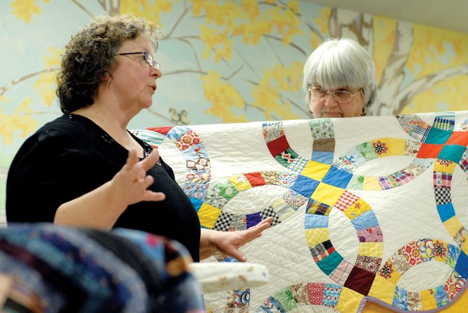 Gladys Battson, left, speaks about her antique quilt collection to a crowd gathered Tuesday at Sunset Meadows I, while Linda Pinnt holds one of the quilts. Battson gave her demonstration at the first meeting of the Craig Quilt Guild, a new group for people who enjoy quilting.