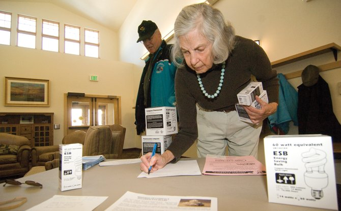 Madeline Weishaar and Gordon Fischer check out a compact fluorescent light bulb giveaway during the senior lunch at the Steamboat Springs Community Center on Monday. A community group, Change We Need, handed out the bulbs to seniors.