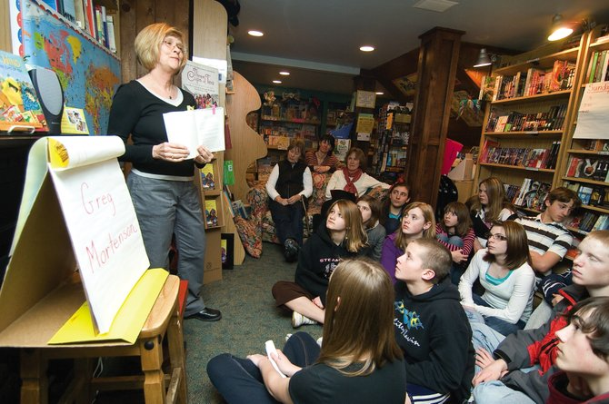 """Vergie DeNucci, a school liaison and owner of Off the Beaten Path Bookstore, talks with a group of eighth-graders Thursday about the book """"Three Cups of Tea,"""" which is the inspiration behind the Pennies for Peace community service project the students will take part in during the next few months."""