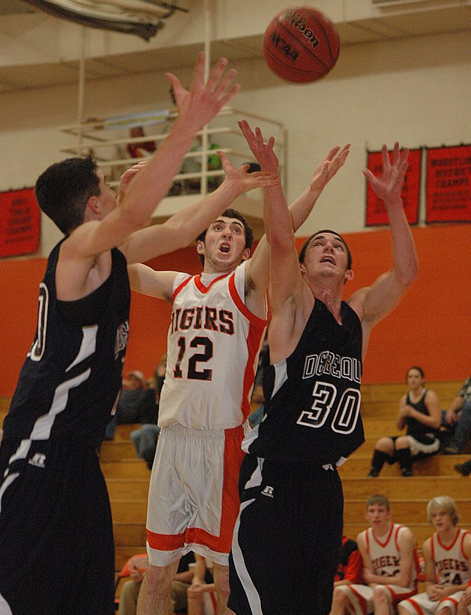 Hayden junior Ben Fulton tries to reach between a pair of De Beque players to snag a rebound last week in the Tigers' 80-50 victory. Hayden will try to carry that momentum into today's game against Paonia.