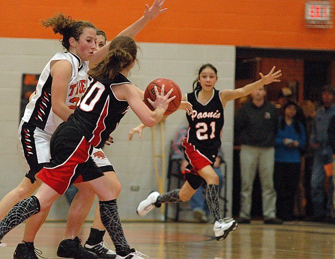 Paonia senior Jami Reed spots a way out of the full-court press defense that Hayden's Caitlin Mahanna, left, and Kylee Sweetser apply late in Friday night's game in Hayden. The Eagles outlasted the Tigers to hand Hayden its first loss of the season, 54-49.