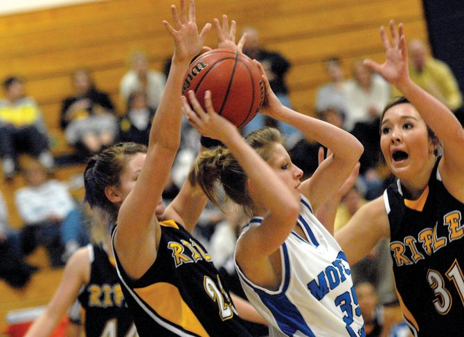 Moffat County High School senior Danette Crofts looks for an opening Saturday against a swarming Rifle High School defense. The Bulldogs took over the top spot in the Western Slope League, with a 58-47 victory against the Bears.