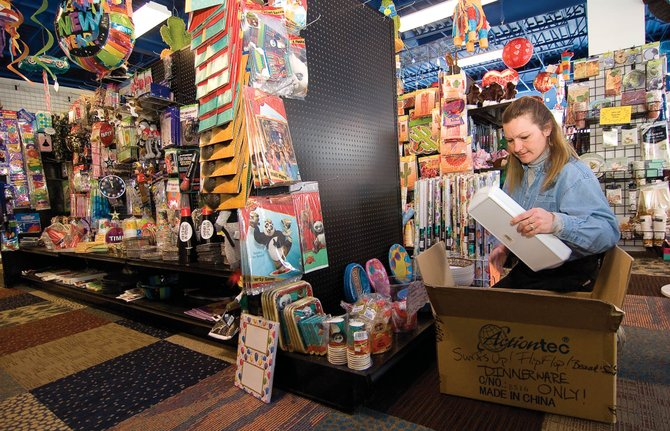 Store manager Carol Herman stocks a shelf at Celebrations, in Central Park Plaza, on Tuesday afternoon. The store is clearing out its inventory by offering as much as 50 percent off of selected merchandise. The store's owner plans to close the store's doors at the end of February.